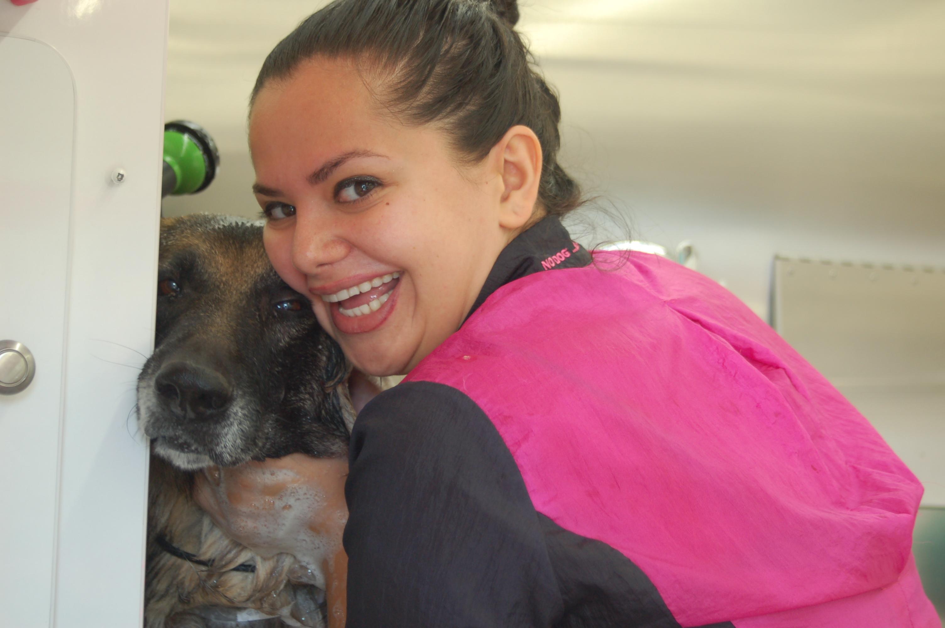 Animal Groomer Amy hugs a dog at a Grooming Station.