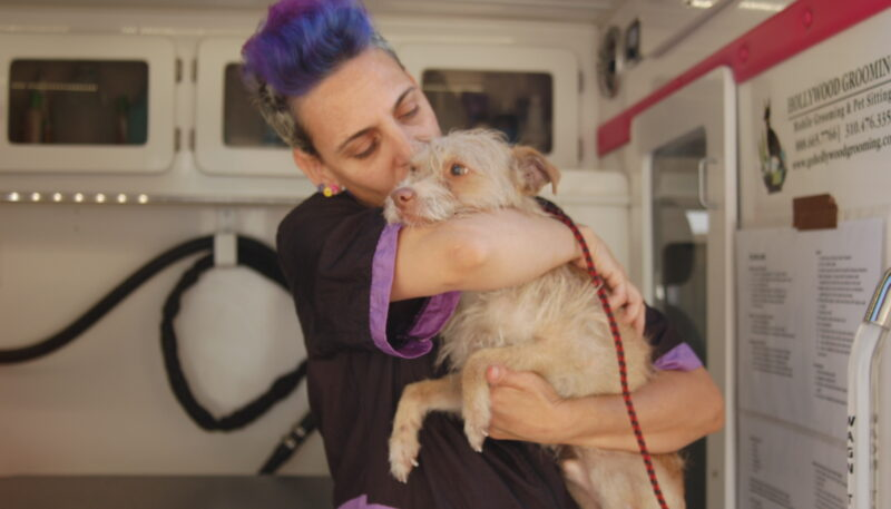 Yael hugs a dog at a Grooming Station at a community event.
