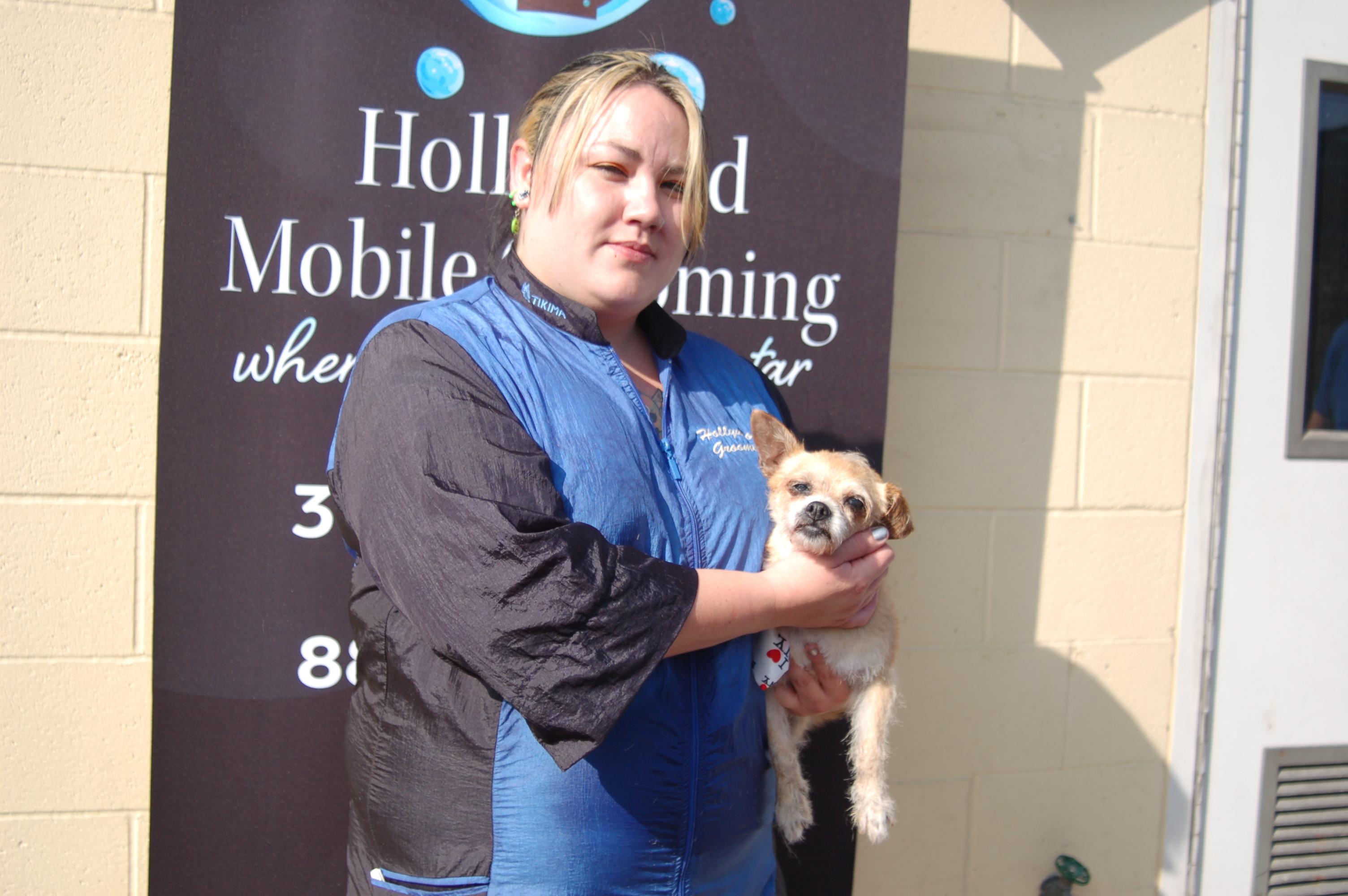 Animal Groomer Katlin holds a small tan and white dog.