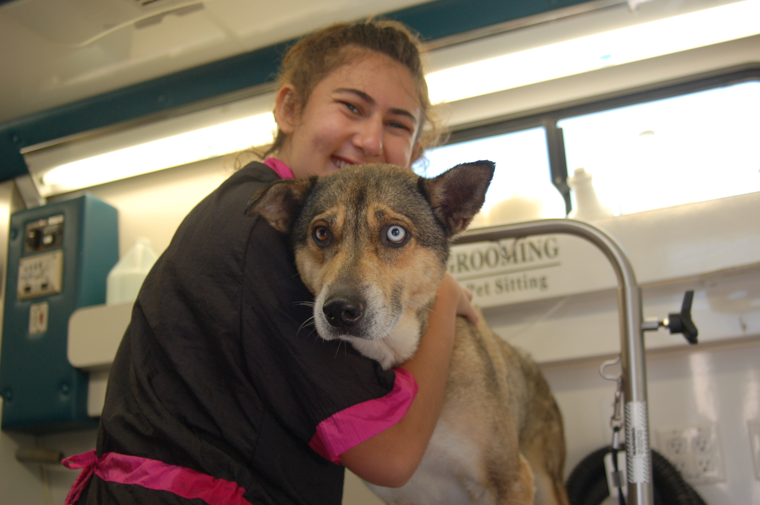 Dog Groomer Danielle hugs a dog at a Grooming Station.