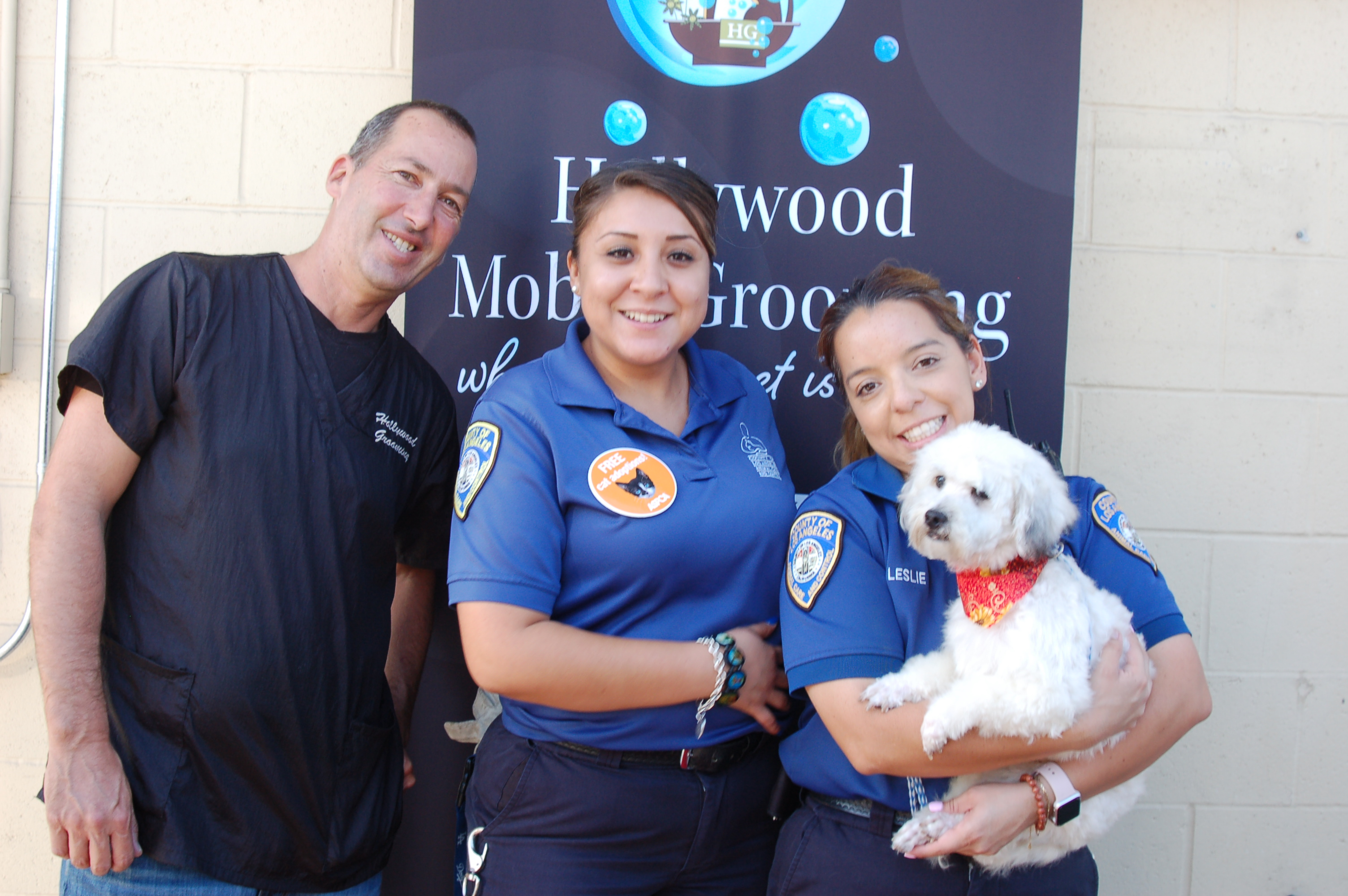 Chuck and team members hold a dog at a Community Event.