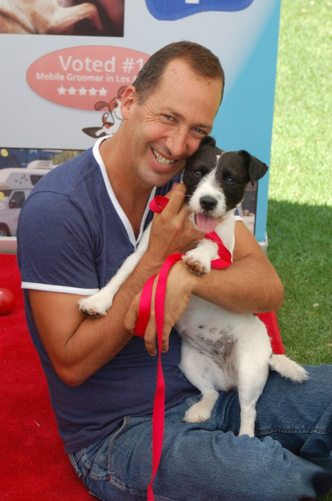 Chuck holds a black and white dog on the red carpet.