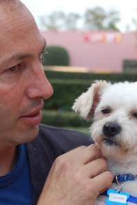 Chuck, Owner of Go Hollywood Grooming holding a small dog.