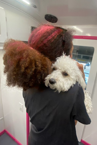 Groomer holding small dog.