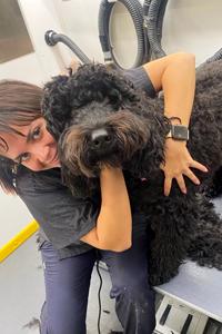 Groomer cuddling large dog.