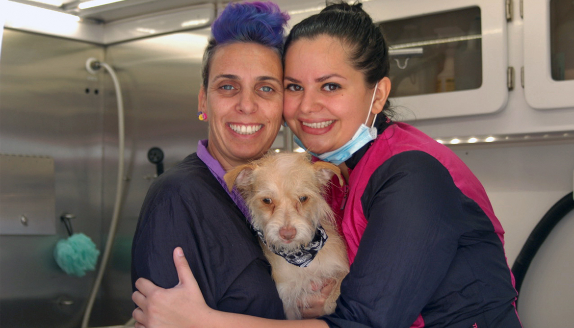 Yael and Amy holding a dog who has just been groomed.